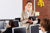 Pretty female high school teacher portrait in computer room — Foto Stock