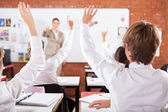 Group of students arms up in classroom — Stock fotografie