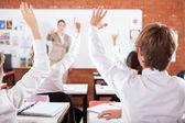 Gruppe von studenten arme oben im klassenzimmer — Stockfoto