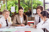 High school teacher helping students in classroom — Stock Photo