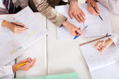 Overhead view of teacher tutoring students in classroom — Stock Photo