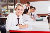 Middle school girl student sitting in classroom — Stock Photo