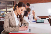 Beautiful school teacher preparing lesson in classroom — Stock Photo