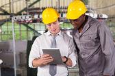 Betriebsleiter und arbeitnehmer blick auf tablet pc — Stockfoto