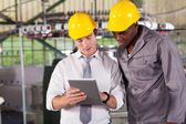 Factory manager and worker looking at tablet computer — Stock Photo