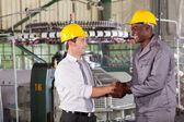 Factory manager handshaking with african american worker — Stock Photo