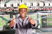 African american textile worker thumbs up in front of weaving loom — Stock Photo