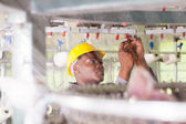African american blue collar worker working in textile factory — Stock Photo
