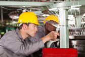 Two textile weaving machine mechanics repairing loom — Stock Photo