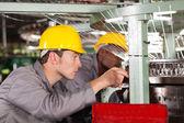 Two textile weaving machine mechanics repairing loom — Stock Photo
