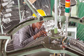 African american textile factory technician repairing weving loom — Stock Photo