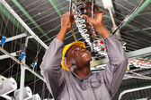 African american textile industrial mechanic repairing weaving loom — Stock Photo