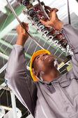 African american textile industrial technician repairing weaving machine — Stock Photo