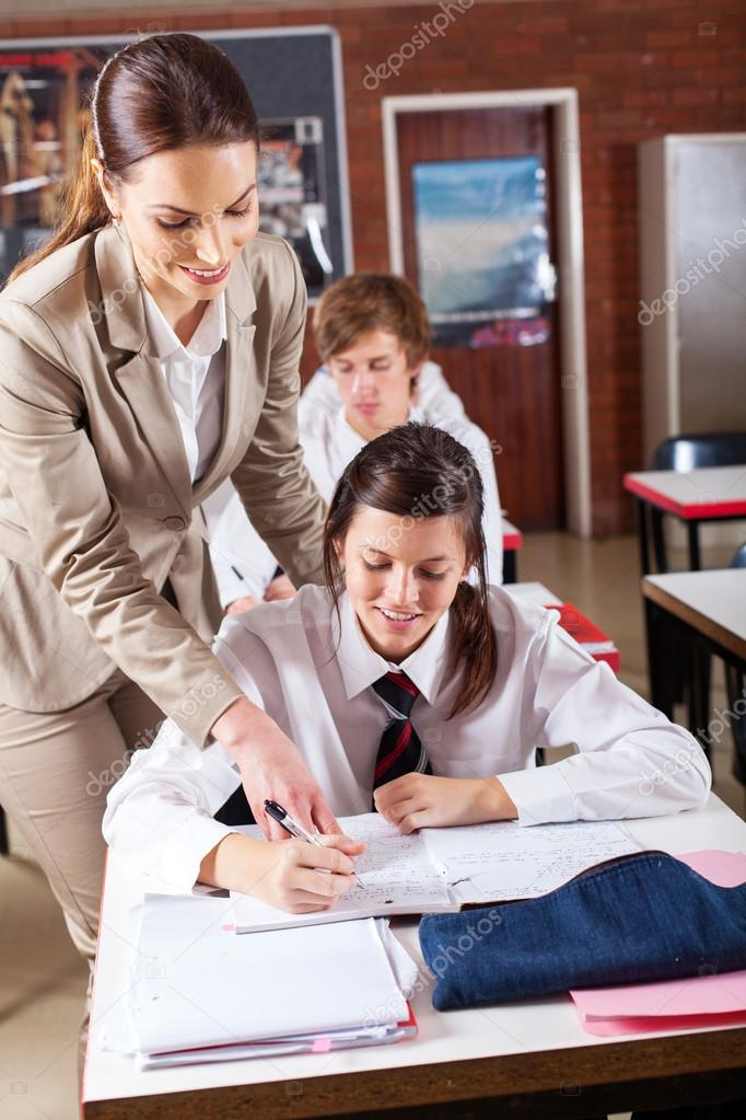 High school teacher helping student in classroom — Stock Photo #14966971