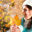 Happy young woman in autumn forest holding golden tree leaves — Stock Photo