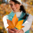 Young woman holding golden tree leaf outdoor in forest — Stock Photo #14970621