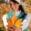 Young woman holding golden tree leaf outdoor in forest — Stock Photo