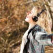 Young woman listening music in autumn forest — Foto Stock