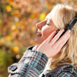 Young woman listening music in autumn forest — Stok fotoğraf