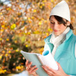 Young beautiful college student reading book in autumn forest — Stock Photo