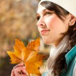 Attractive woman with golden autumn leaves in forest — Stock Photo