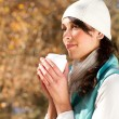 Attractive woman drinking coffee in autumn forest — Stock Photo