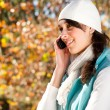 Stock Photo: Beautiful woman using mobile phone in autumn forest