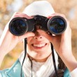 Young woman using binoculars in autumn forest — Stock Photo #14970699