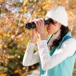 Stock Photo: Young womusing binoculars in autumn forest