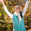 Happy woman throwing autumn leaves in forest — Stock Photo