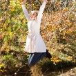 Happy young woman jumping in autumn forest - Stockfoto