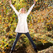 Happy young woman jumping in autumn forest — Stock Photo #14970811