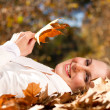 Happy woman lying on autumn leaves — Foto de stock #14970865