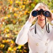Young woman using binoculars in autumn forest — Stock Photo #14970867
