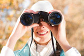 Young woman using binoculars in autumn forest — Stock Photo