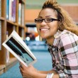 Happy african american college girl reading book in library - Stock Photo
