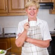 Happy senior woman relaxing in home kitchen — Stock Photo #15604431