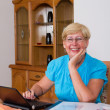 Happy senior woman working on home finance — Stock Photo