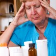 Stock Photo: Depressed senior womwith medicine or health problem