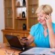 Senior woman buying online and paying with credit card — Stok fotoğraf