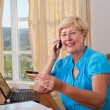 Stock Photo: Senior woman buying online and paying with credit card