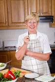 Happy senior woman relaxing in home kitchen — Foto Stock