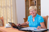 Happy senior woman calculating her finance at home — Stock Photo