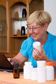 Senior woman researching and buying medicines online — Stock Photo