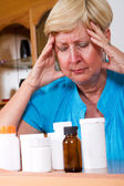 Depressed senior woman with medicine or health problem — Stock Photo
