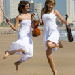 Two happy female violinists jumping on beach — Stok fotoğraf