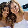 Two happy friends taking photos on beach with cell phone - Stock Photo