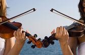 Deux jeunes femmes jouant le violon sur la plage — Photo