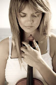 Thoughtful female violinist with violin on beach — Stock Photo