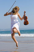 Joyful female violinist jumping on beach — Stock Photo